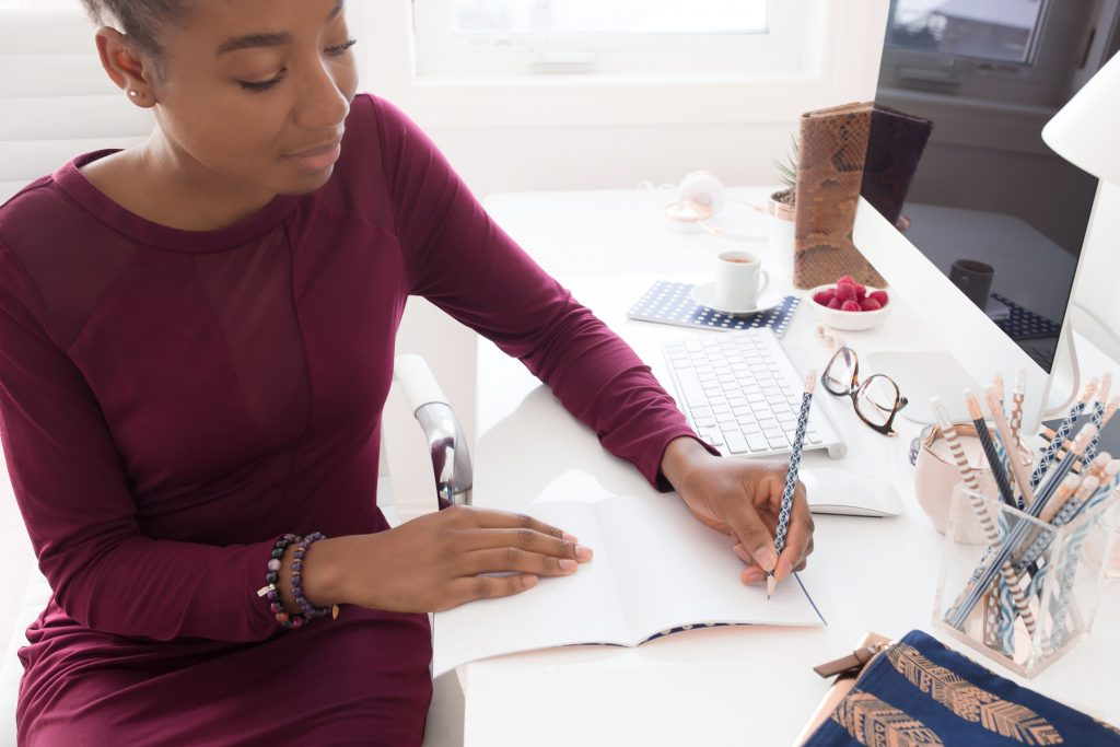 Brand Strategy by popular US graphic and web designers for small businesses, Bea and Elle: image of a woman sitting at a white office desk and writing in a notebook with a pencil.